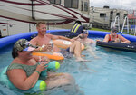 Race fans, from left to right, Lauren Hopkins, J.D. Johnson, Aaron Hopkins and Michelle Johnson cool off in a pool in the infield before a NASCAR Cup Series auto race at Daytona International Speedway, Saturday, July 6, 2019, in Daytona Beach, Fla. (AP Photo/Phelan Ebenhack)