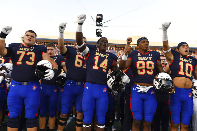 """Navy players raise their fists after singing """"Navy Blue and Gold"""" after an NCAA college football game against Air Force, Saturday, Sept. 11, 2021, in Annapolis, Md. (AP Photo/Terrance Williams)"""