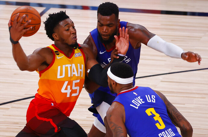 Utah Jazz's Donovan Mitchell drives against Denver Nuggets' Paul Millsap and Torrey Craig (3) during the fourth quarter of Game 4 of an NBA basketball first-round playoff series, Sunday, Aug. 23, 2020, in Lake Buena Vista, Fla. (Kevin C. Cox/Pool Photo via AP)
