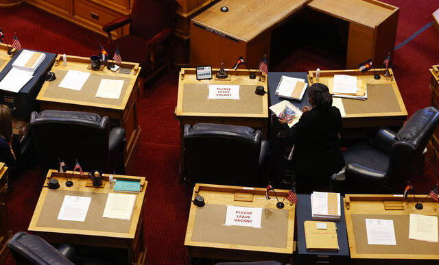 A clerk puts out bills on the desks of members in the House of Representatives Senate as lawmakers reconvene the session that was suspended in mid-March by the spread of new coronavirus Tuesday, May 26, 2020, in Denver. Lawmakers are facing the need to make drastic cuts in the state budget to deal with the tax shortfall stemming from the pandemic's effects on business. (AP Photo/David Zalubowski)
