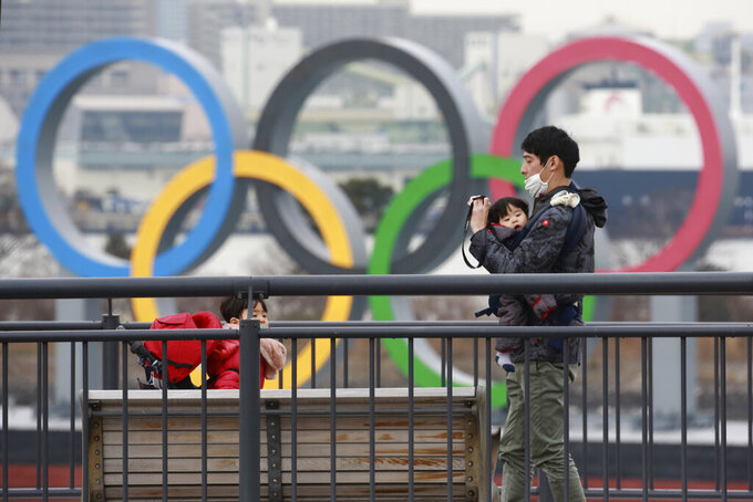 People wearing face masks to protect against the spread of the coronavirus stand at the Odaiba waterfront as Olympic rings is seen in the background in Tokyo, Tuesday, Jan. 26, 2021. (AP Photo/Koji Sasahara)