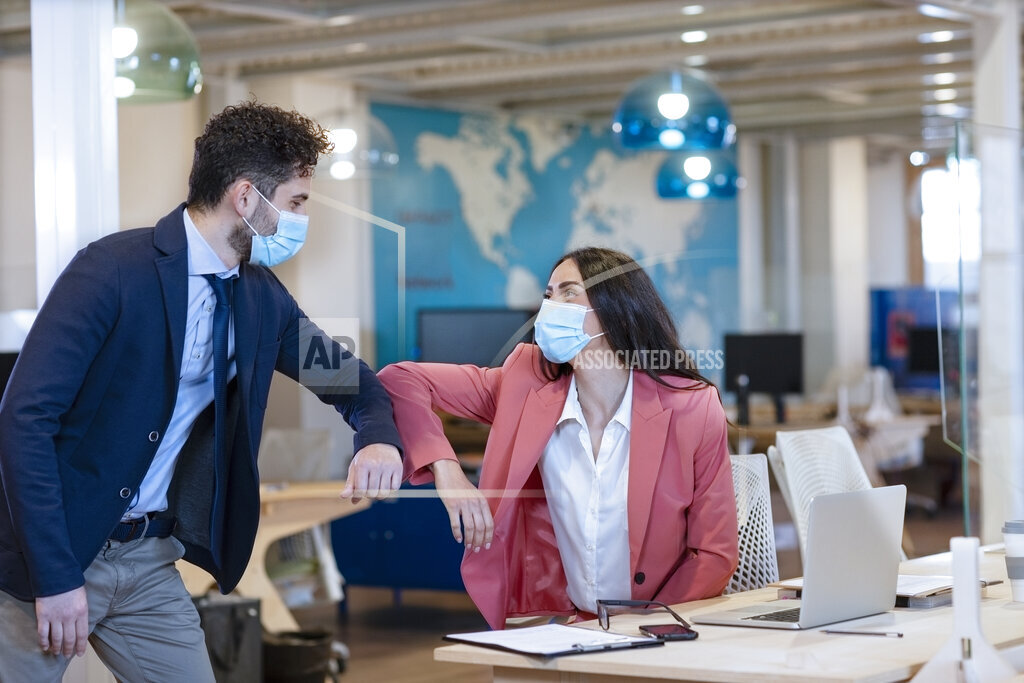 Male and female entrepreneurs doing elbow bump during pandemic at office