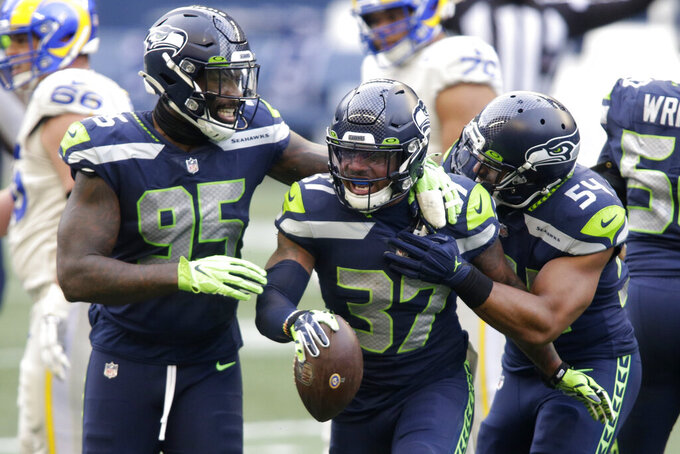 Seattle Seahawks free safety Quandre Diggs (37) reacts with defensive end Benson Mayowa (95) and linebacker Bobby Wagner (54) after Diggs intercepted a pass during the first half of an NFL football game against the Los Angeles Rams, Sunday, Dec. 27, 2020, in Seattle. (AP Photo/Scott Eklund)