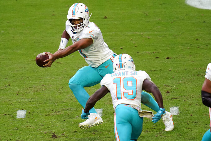 Miami Dolphins quarterback Tua Tagovailoa (1) fakes a hand off to wide receiver Jakeem Grant (19) during the first half of an NFL football game against the Arizona Cardinals, Sunday, Nov. 8, 2020, in Glendale, Ariz. (AP Photo/Ross D. Franklin)