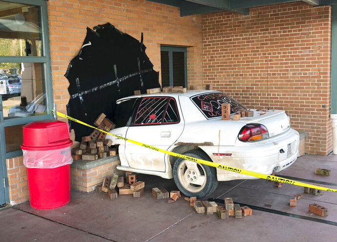 This photo taken Wednesday, May 16, 2018, and provided by Ritchie Narges, shows what looks to be a car that crashed into the principal's office at Cumberland High School in Cumberland, Wis., but is actually an illusion created for a senior class prank. Students at the school used a junk car, some bricks, some tape and a black tarp to make it look like the car had crashed into their school. Police arrived on the scene only to realize it wasn't really a wreck. The police department wrote on Facebook that it was