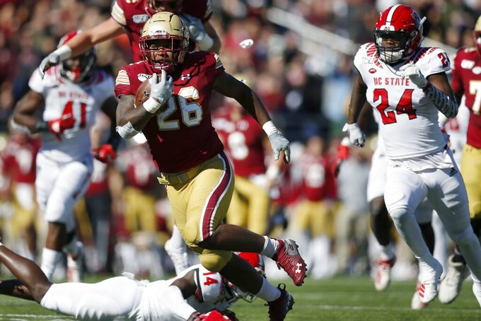 Boston College running back David Bailey (26) evades North Carolina State safety De'Von Graves (14) on a touchdown run during the first half of an NCAA college football game in Boston, Saturday, Oct. 19, 2019. (AP Photo/Michael Dwyer)