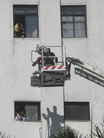 People awaiting rescue stand near the windows of a nine-story building with offices of a state-run telephone company during a fire in Mumbai, India, Monday, July 22, 2019. (AP Photo/Rafiq Maqbool)