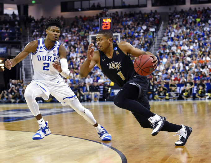 CORRECTS TO SECOND ROUND NOT FIRST Central Florida's BJ Taylor (1) drives down the baseline while defended by Duke's Cam Reddish (2) during the first half of a second round men's college basketball game in the NCAA Tournament in Columbia, S.C. Sunday, March 24, 2019. (AP Photo/Richard Shiro)