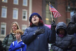 Carol Hutchins holds an American flag while singing the national anthem at a Veterans Day event honoring Mainers who served in the military, Monday, Nov. 11, 2019, in Portland, Maine. Hutchins' father fought in the Battle of the Bulge during World War II. (AP Photo/Robert F. Bukaty)