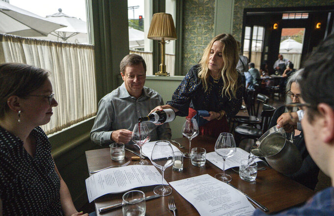 """In this Saturday, June 19, 2021, photo, Caroline Styne, owner and wine director at The Lucques Group, serves wine to attorney Alec Nedelman, celebrating early """"Father's Day """"with his family at the A.O.C. Brentwood restaurant in Los Angeles. Styne has turned away dozens of customers at the company's A.O.C. West Hollywood restaurant because she doesn't have the staff to serve them, leaving seats empty. (AP Photo/Damian Dovarganes)"""