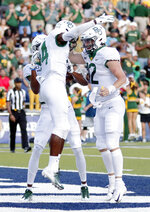Baylor wide receiver Tyquan Thornton, back left, wide receiver Chris Platt (14) and quarterback Charlie Brewer (12) celebrate Platt's touchdown during the first half of an NCAA college football game against Rice on Saturday, Sept. 21, 2019, in Houston. (AP Photo/Michael Wyke)