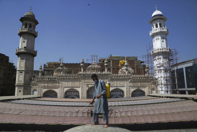 A volunteer disinfects the outer area of a historical Mohabat Khan mosque ahead of the upcoming Muslim fasting month of Ramadan, in Peshawar, Pakistan, Friday, April 9, 2021. (AP Photo/Muhammad Sajjad)