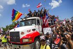 Sitting atop the cab of a truck Ricky Martin, flying a gay pride flag, joins other Puerto Rico celebrities and demonstrators in a protest to demand the resignation of Governor Ricardo Rossello from office, in San Juan, Puerto Rico, Monday, July 22, 2019. Protesters are demanding Rossello step down for his involvement in a private chat in which he used profanities to describe an ex-New York City councilwoman and a federal control board overseeing the island's finance. (AP Photo/Dennis M. Rivera Pichardo)