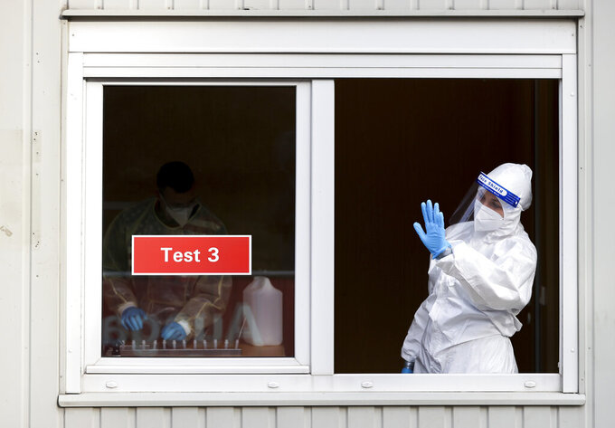 A woman in protective clothing beckons test takers to her window at a test center with the start of the model project in ugustusburg, Germany, Thursday, April 1, 2021. After five months of lockdown, hotels and restaurants here have reopened to private visitors.  ( Jan Woitas/dpa via AP)