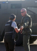 A member of the Tennessee Highway Patrol Special Operations Unit, right, hands an item to Henry County Sheriff's Sgt. Michelle Brewer Monday, June 1, 2020 after the unit had been on the scene to help in Monday's standoff at Indoor Comfort in Springville, Tenn. (Ken Walker/The Paris Post-Intelligencer via AP)