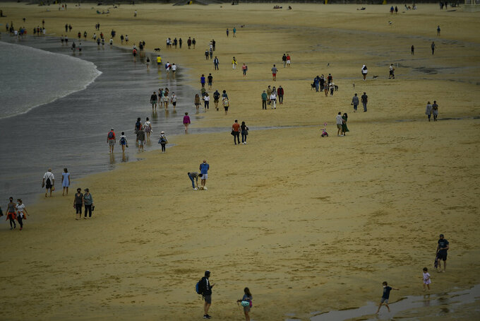 People walk along La Concha beach, after lockdown restrictions were lifted, in San Sebastian, northern Spain, Sunday, May 9, 2021. Impromptu street celebrations erupted across Spain as the clock struck midnight on Saturday, when a six-month-long national state of emergency to contain the spread of coronavirus ended and many nighttime curfews were lifted. (AP Photo/Alvaro Barrientos)