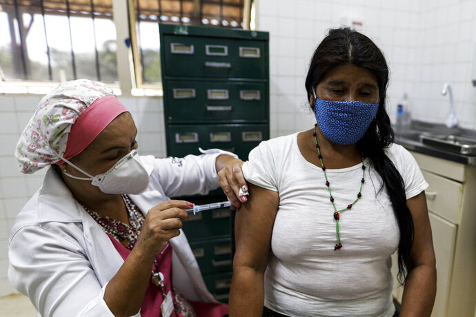 An Tenonde Pora Indigenous woman gets a shot of China's Sinovac CoronaVac vaccine for COVID-19 in Tenonde Pora village, on the outskirts of Sao Paulo, Brazil, Wednesday, Jan. 20, 2021. (AP Photo/Marcelo Chello)