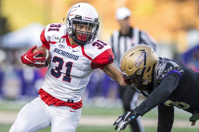 Richmond running back Savon Smith (31) fends off James Madison safety Wayne Davis (8) during the first half of an NCAA football game in Harrisonburg, Va, Saturday, Nov. 16, 2019. (Daniel Lin/Daily News-Record via AP)