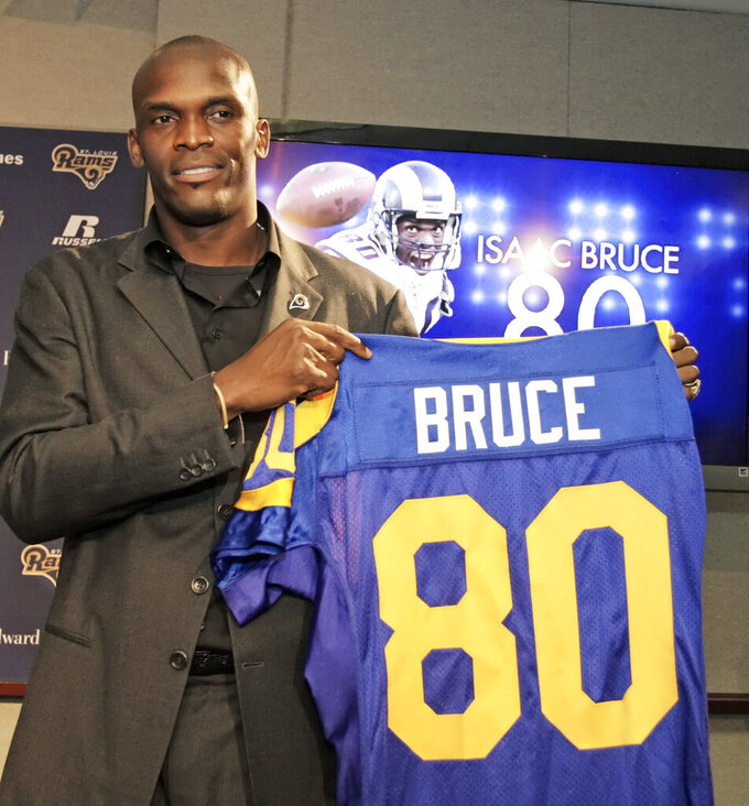 FILE - St. Louis Rams' Isaac Bruce holds up his jersey number at the news conference to announce his retirement from professional football after 16 years in the NFL, in St. Louis, in this Wednesday, June 9, 2010, file photo. Bruce will become the fourth member of the Rams' high-scoring offense to be enshrined in the Pro Football Hall of Fame next month, following running back Marshall Faulk (2011), left tackle Orlando Pace (2016) and quarterback Kurt Warner (2017). Bruce is part of the 2020 class, whose entry was delayed a year because of the coronavirus pandemic. (AP Photo/Tom Gannam, File)