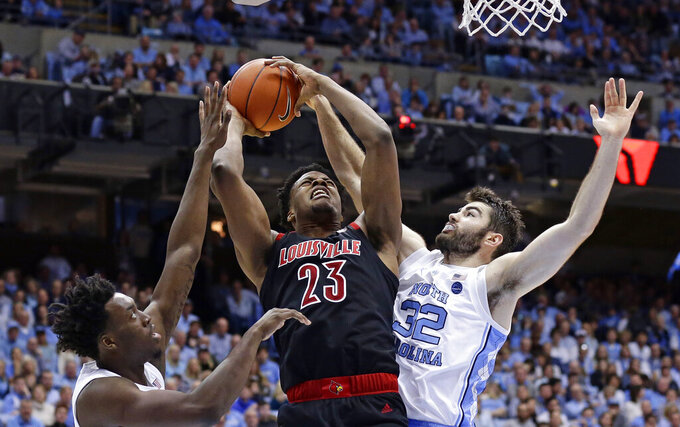 Louisville's Steven Enoch (23) drives to the basket while North Carolina's Luke Maye (32) and Nassir Little defend during the second half of an NCAA college basketball game in Chapel Hill, N.C., Saturday, Jan. 12, 2019. Louisville won 83-62. (AP Photo/Gerry Broome)