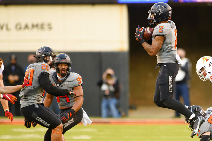 Oklahoma State's Demarco Jones (22) and Trace Ford (94) watch as teammate Tylan Wallace (2) leaps to grab an Iowa State onside kick in the final seconds of an NCAA college football game Saturday, Oct. 24, 2020, in Stillwater, Okla. (AP Photo/Brody Schmidt)