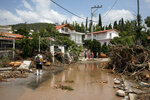 A man walks at a street full of debris following a storm at the village of Politika, on Evia island, northeast of Athens, on Sunday, Aug. 9, 2020. Five people have been found dead and dozens have been trapped in their homes and cars from a storm that has hit the island of Evia, in central Greece, police say. (AP Photo/Yorgos Karahalis)