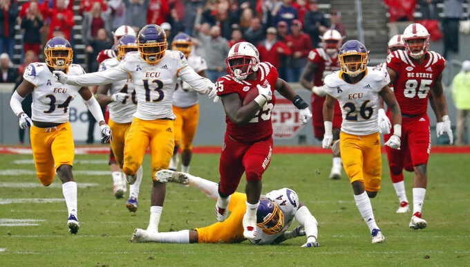 North Carolina State's Reggie Gallaspy II (25) breaks away from East Carolina's Myles Berry (34), Davondre Robinson (13), Kendall Futrell (44) and Colby Gore (26) for a long gain during the second half of NCAA college football game in Raleigh, N.C., Saturday, Dec. 1, 2018. (AP Photo/Chris Seward)