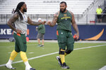 FILE - In this March 16, 2019, file photo, Arizona Hotshots offensive linemen Josh Allen, left, and Hugh Thornton warm up before an AAF football game against the Orlando Apollos Saturday, March 16, 2019, in Orlando, Fla.  Thornton is attempting to complete an NFL comeback with the Washington Redskins that would be a major milestone in a lifelong journey full of adversity. (AP Photo/Phelan M. Ebenhack, File)
