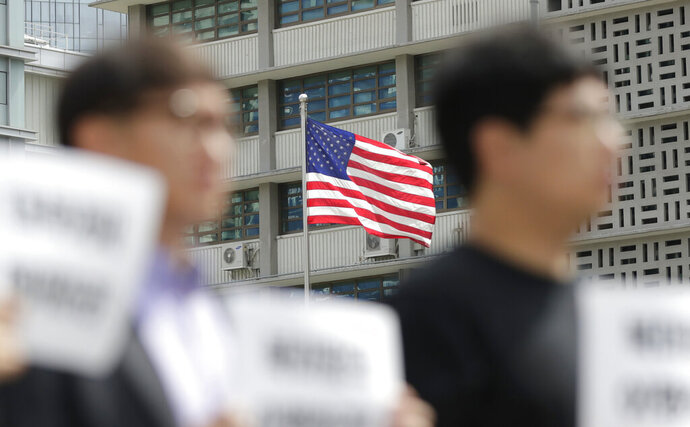 U.S. flag is seen as protesters hold a rally demanding the peace on the Korean peninsula and to stop sanctions on North Korea, ahead of U.S. President Donald Trump's scheduled visit near the U.S. embassy in Seoul, South Korea, Thursday, June 27, 2019. North Korea said Thursday South Korea must stop trying to mediate between Pyongyang and Washington. The North's Foreign Ministry also repeated its demand that the United States must work out mutually acceptable proposals to salvage a deadlocked nuclear negotiations by the end of December. (AP Photo/Lee Jin-man)