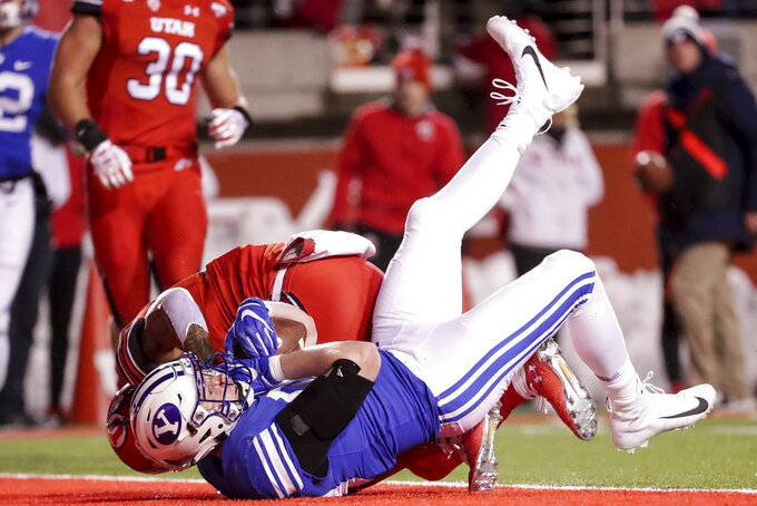 Brigham Young tight end Matt Bushman (89) falls into the end zone after making a reception ahead of Utah defensive back Corrion Ballard (15) during an NCAA college football game in Salt Lake City on Saturday, Nov. 24, 2018. (Spenser Heaps/The Deseret News via AP)