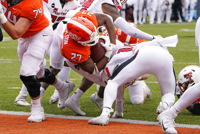 Oklahoma State running back Dezmon Jackson (27) scores against Texas Tech in the first half of an NCAA college football game in Stillwater, Okla., Saturday, Nov. 28, 2020. (AP Photo/Sue Ogrocki)