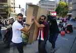 Anti-government protesters remove their belongings as they open a main highway they closed for more then ten days during protests, in Beirut, Lebanon, Wednesday, Oct. 30, 2019. Lebanese banks have been closed for the last two weeks as the government grapples with mass demonstrations that have paralyzed the country, but an even greater crisis may set in when they reopen Friday. (AP Photo/Hussein Malla)