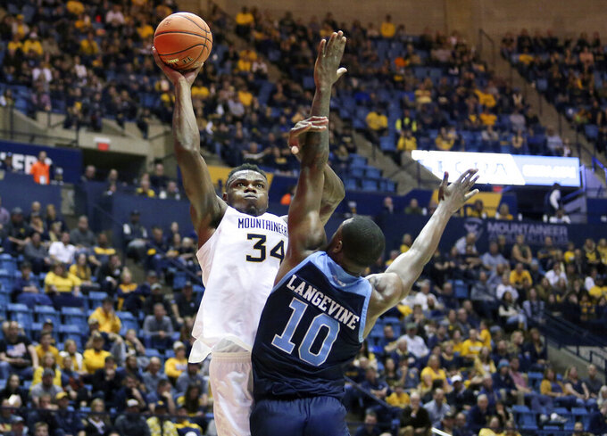 West Virginia forward Oscar Tshiebwe (34) goes to  shoots as he is defended by Rhode Island forward Cyril Langevine (10) during the second half of an NCAA college basketball game Sunday, Dec. 1, 2019, in Morgantown, W.Va. (AP Photo/Kathleen Batten)