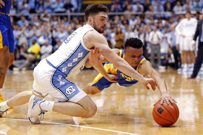 North Carolina guard Andrew Platek (3) and Pittsburgh guard Trey McGowens (2) dive for a loose ball during the second half of an NCAA college basketball game in Chapel Hill, N.C., Wednesday, Jan. 8, 2020. (AP Photo/Gerry Broome)