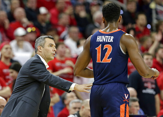 Virginia coach Tony Bennett speaks with De'Andre Hunter (12) during the first half of the team's NCAA college basketball game against North Carolina State in Raleigh, N.C., Tuesday, Jan. 29, 2019. (AP Photo/Gerry Broome)