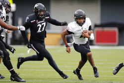 Army quarterback Christian Anderson, right, cuts up field past Cincinnati linebacker Darrian Beavers during the first half of an NCAA college football game Saturday, Sept. 26, 2020, in Cincinnati, Ohio. (AP Photo/Jay LaPrete)