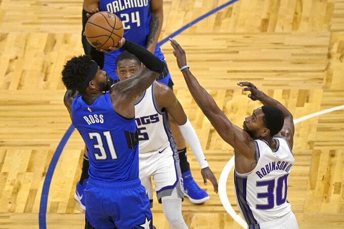 Orlando Magic guard Terrence Ross (31) shoots in front of Sacramento Kings guard De'Aaron Fox (5) and forward Glenn Robinson III (30) during the second half of an NBA basketball game Wednesday, Jan. 27, 2021, in Orlando, Fla. (AP Photo/Phelan M. Ebenhack)