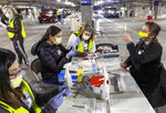FILE - In this Jan. 10, 2021, file photo, medical professionals from Oregon Health & Science University load syringes with the Moderna COVID-19 vaccine at a drive-thru vaccination clinic in Portland, Ore. The role that race should play in deciding who gets priority for the COVID-19 vaccine in the next phase of the rollout is being put to the test in Oregon. An advisory committee will vote Thursday, Jan. 28, 2021, on whether to prioritize people of color, target those with chronic medical conditions or some combination. (Kristyna Wentz-Graff/Pool Photo via AP, File)