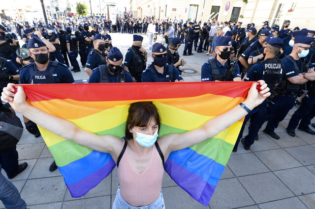 A women holds a rainbow flags as she stands in front of a police line during a protest against a demonstration of far-right activists in Warsaw, Poland, Sunday, Aug. 16, 2020. The far-right activists protest against LGBT rights. Tensions over LGBT rights have been growing in Poland after an increasingly visible gay rights movement has been met by an angry backlash from the church and the government. (Photo/Czarek Sokolowski)