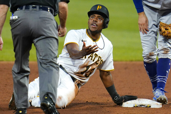 Pittsburgh Pirates' Ke'Bryan Hayes (13) appeals to umpire Dan Iassogna, left, after sliding past second base and being tagged out by Los Angeles Dodgers second baseman Chris Taylor during the third inning of a baseball game in Pittsburgh, Tuesday, June 8, 2021. Hayes remained out and the inning ended. (AP Photo/Gene J. Puskar)
