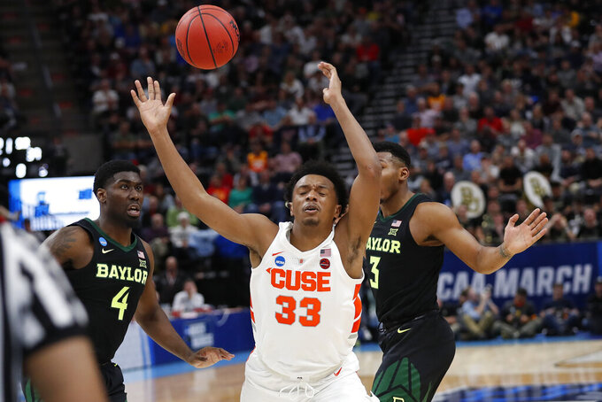 Syracuse forward Elijah Hughes (33) is tripped up by Baylor guard Mario Kegler (4) and guard King McClure (3) during the second half of a first-round game in the NCAA men's college basketball tournament Thursday, March 21, 2019, in Salt Lake City. (AP Photo/Jeff Swinger)