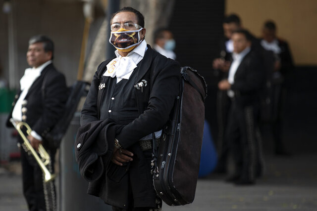 Mariachis, some wearing protective face  masks, wait for clients in Plaza Garibaldi, where residents come to hire mariachis for events and parties, in Mexico City, Friday, July 17, 2020. With large gatherings cancelled and concerns over singing inside closed spaces, work has plummeted for the hundreds of Mariachis based in Plaza Garibaldi. Those lucky enough to get occasional work say they are playing for small celebrations at home, such as birthdays or proposals, as well as at wakes for the deceased. (AP Photo/Rebecca Blackwell)
