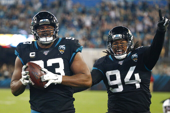 Jacksonville Jaguars defensive end Calais Campbell (93) scores a touchdown as defensive end Dawuane Smoot (94) celebrates after Campbell recovered a fumble by Indianapolis Colts quarterback Jacoby Brissett during the second half of an NFL football game, Sunday, Dec. 29, 2019, in Jacksonville, Fla. (AP Photo/Stephen B. Morton)