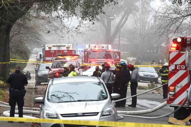 Officials clean up the scene following a small plane crash during dense fog in a residential neighborhood on Wednesday, Jan. 13, 2021, in Columbia, S.C. Authorities say the woman in the home was able to get out safely and have not given information on the condition of anyone aboard the plane. (AP Photo/Meg Kinnard)