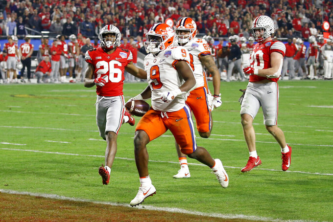 FILE - In this Dec. 28, 2019, file photo, Clemson running back Travis Etienne scores a touchdown against Ohio State during the second half of the Fiesta Bowl NCAA college football playoff semifinal, in Glendale, Ariz. Etienne was selected to The Associated Press preseason All-America first-team, Tuesday, Aug. 25, 2020.  (AP Photo/Ross D. Franklin, File)