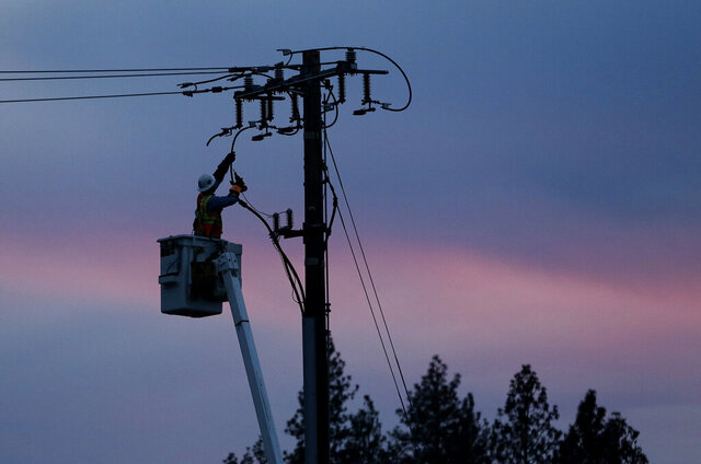FILE - In this Nov. 26, 2018, file photo, a Pacific Gas & Electric lineman works to repair a power line in fire-ravaged Paradise, Calif. California regulators will consider suspending a $200 million fine against Pacific Gas & Electric for neglecting electrical equipment that killed more than 100 people. If PG&E is granted the waiver to help it emerge from bankruptcy, it will deprive California of desperately needed money as a pandemic-driven recession depletes state revenue from sales and income taxes. (AP Photo/Rich Pedroncelli, File)
