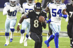 FILE - Baltimore Ravens quarterback Lamar Jackson (8) runs the ball for a first half touchdown during an NFL football game against the Dallas Cowboys in Baltimore, in this Tuesday, Dec. 8, 2020, file photo. Buffalo's Josh Allen and Baltimore's Lamar Jackson become the first quarterbacks of the five-member 2018 first-round draft class set to meet in the playoffs as the Bills prepare to face the Ravens in the AFC divisional round on Saturday night. (AP Photo/Terrance Williams, File)