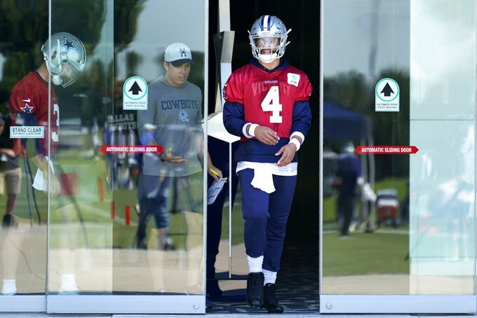 Dallas Cowboys quarterback Dak Prescott (4) walks onto the field followed by offensive coordinator Kellen Moore and practice squad quarterback Ben DiNucci (3) at the team's NFL football training facility in Frisco, Texas, Thursday, Sept. 23, 2021. (AP Photo/Tony Gutierrez)