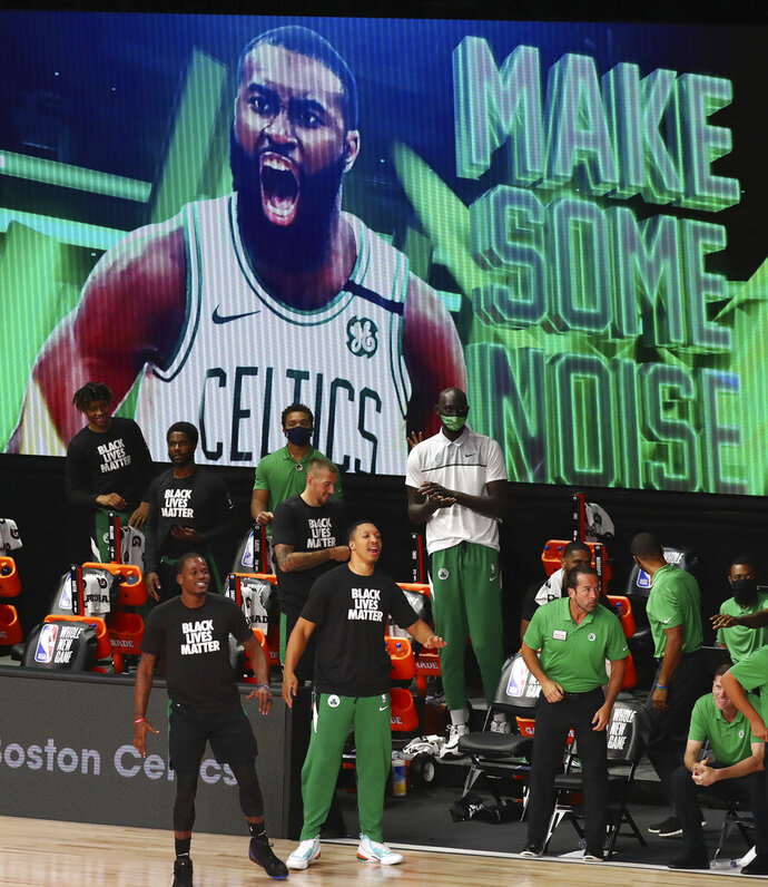 Boston Celtics bench reacts after guard Jaylen Brown (not pictured) makes a basket against the Orlando Magic during the first half of an NBA basketball game Sunday, Aug. 9, 2020, in Lake Buena Vista, Fla. (Kim Klement/Pool Photo via AP)