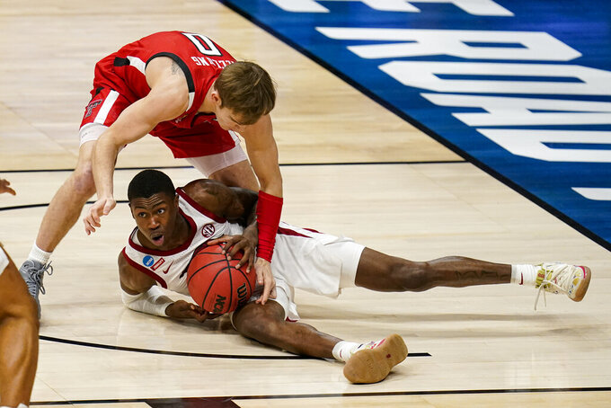 Arkansas guard Davonte Davis (4) tries to pick up a loose ball under Texas Tech guard Mac McClung (0) in the first half of a second-round game in the NCAA men's college basketball tournament at Hinkle Fieldhouse in Indianapolis, Sunday, March 21, 2021. (AP Photo/Michael Conroy)